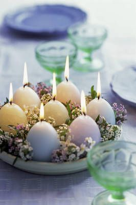 Beautiful Easter Center Piece  Egg-shaped candles can be found at the dollar store, but when combined with a simple planter tray and a few flowers, this inexpensive Easter centerpiece really glows.