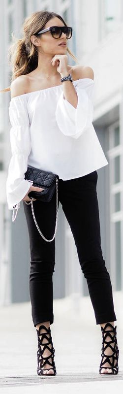 Lydia Lise Millenis wearing a classic off the shoulder blouse here, looking elegant and sophisticated in a monochrome style consisting of black cigarette trousers and black sandals.