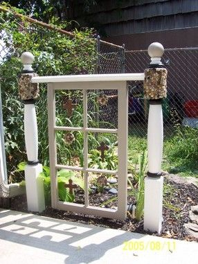"""""""Then I needed a visual divider between my vegetable garden and collection of hostas so I took 3 windows (also removed the glass). I positioned them on their sides, hung beads and crystals in the center of each pane and attached them on the top and bottom with 2x4 for stability. They serve as a low wall"""""""