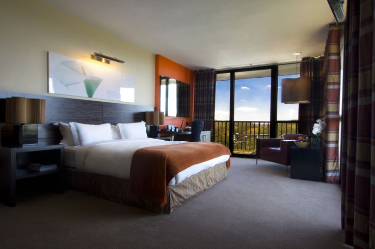 Luxury Bedroom - Orange: These suites have large floor to ceiling windows overlooking the rolling landscape of the Klipriviersberg; they are located in the bush area of Thaba Ya Batswana ensuring quiet privacy. Each air-conditioned suite is equipped with large screen LCD television, and iPod docking station.