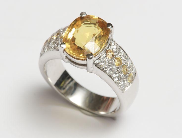 Bague en or gris, 750 MM, ornée d'un saphir jaune ovale pesant 4 carats environ épaulé de saphirs jaunes et diamants, , taille : 53, poids : 8,5gr. brut.  Estimation : 2.000/2.200€