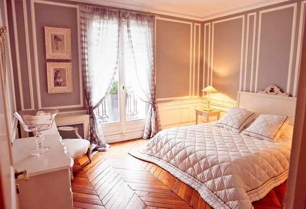 Love the trim on the walls! Parisian Style Bedroom With Hardwood Floors
