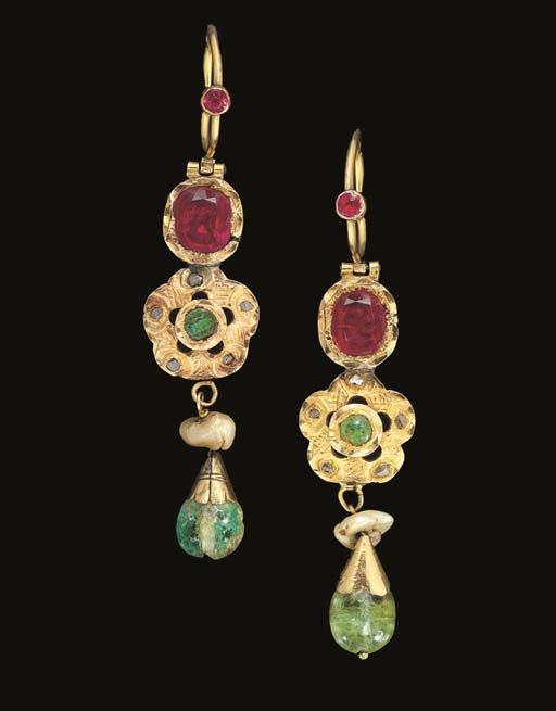 Lot Description  A PAIR OF MOROCCAN RUBY AND DIAMOND INSET EARRINGS   19TH CENTURY   Each with a large ruby within bright cut surround above a gold rosette, the centre and each petal inset with an emerald, the interstices bright cut, a rough pearl and emerald drop pendant below, hoop above with applied ruby