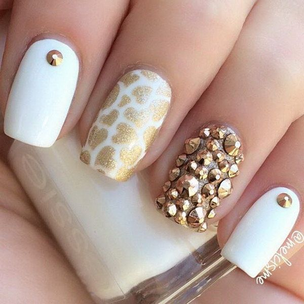 Creative looking white and gold nail art design with embellishments. The nails uses white nail polish as the base design, the wonderful embellishments on top make it even more appealing to the eyes with the combination of gold glitter polish to form shapes on top.
