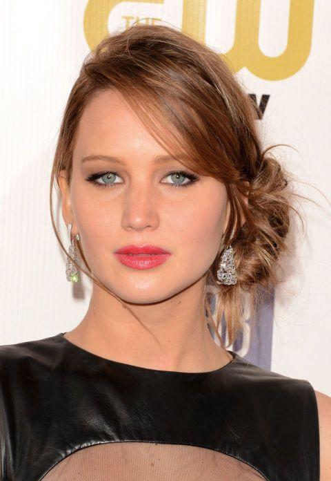 El recogido ladeado, como el de Jennifer, es elegante y uno de los más demandados. Alisa el cabello y, con la raya al lado, haz un recogido ayudándote de una goma o pasador. Deja escapar algún mechón. Fija con laca fuerte. La interprete apuesta por un maquillaje suave dando el punto de color en los labios.