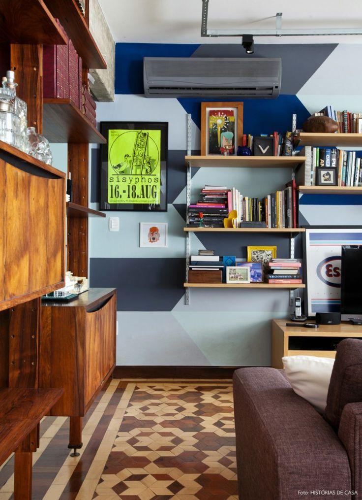Sala de estar divertida e aconchegante: parede com pintura geométrica em tons de azul, prateleiras recheadas de livros e piso com mosaico.