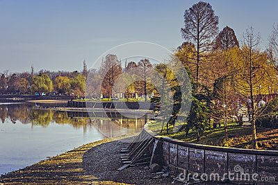 Sunny peaceful scenery with people relaxing on the banks of the Herastrau lake drained for maintenance during springtime.