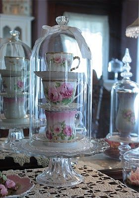 A tall stack of romantically pretty tea cups nestled under a cloche, what's not to love? #teacup #tea #party #kitchen #vintage #shabby #chic #cloche