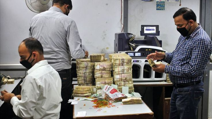 PAPER MONEY: Bank employees count old 500 Indian rupee banknotes inside a bank in Jammu
