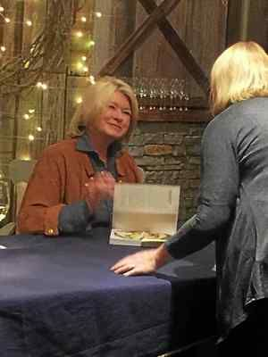 "Martha Stewart asks the name of a customer at terrain's in Glen Mill Friday night during a cocktail party/book-signing event to promote ""Martha Stewart's Slow Cooker,"" her latest book. About 250 fans stood in line for an hour or two to get a few seconds with the famous entrepreneur."
