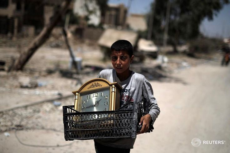 A displaced Iraqi boy carries a clock as he flees from western Mosul, Iraq May 31, 2017. U.S.-backed Iraqi government forces retook eastern Mosul in January and began a new push on Saturday to capture the group's remaining enclave in western Mosul, comprising of the Old City center where the mosque is located, and three adjacent districts alongside the western bank of the River Tigris. Up to 200,000 people still live in harrowing conditions behind Islamic State lines in Mosul, running low on…