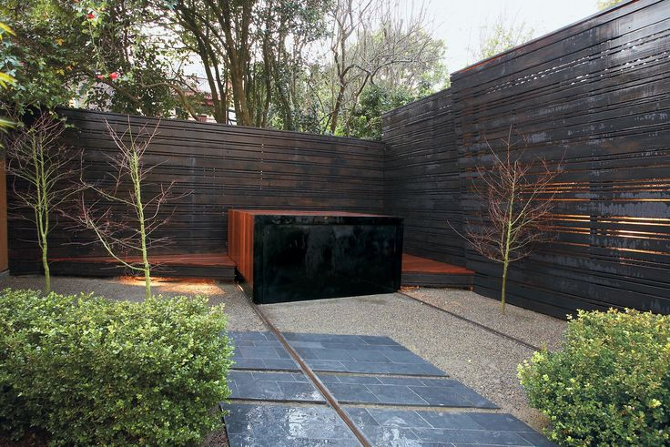 These 11 Modern Fences Bring a Whole New Meaning to Curb Appeal - Photo 6 of 11 - More than just a clever cover, the ipe wood shell of Mark Erman's spa, thanks to its 40-foot tracks, niftily navigates the rocky straights between spa shelter, dapper deck, and bespoke buffet table.