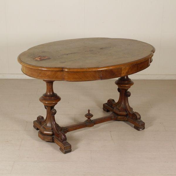 Tavolo a biscotto retto da balaustri torniti con lesene intagliate raccordati da traversa. Piano sagomato con riserva quadripartita.