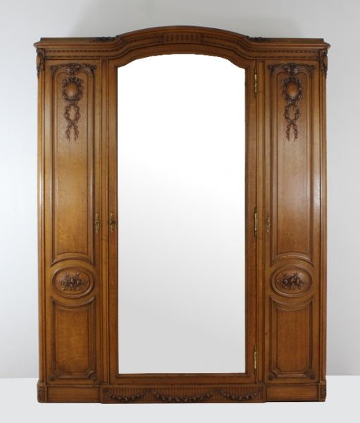 This fantastic grand French Armoire is made from solid Oak with rich carvings and adornments. Generous in size it has the main middle door with a wide bevelled mirror behind which is hanging space as well as 2 smaller doors on the side behind which are shelves. All original with its original hardware and almost an antique (dates 1920's.). This item is sourced from the markets and farmhouses in France. One only available. #Armoire #Armoires