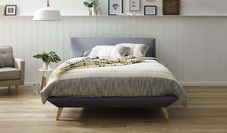Contemporary chic retro bed upholstered in linen and complimented by modern scandinavian timber legs