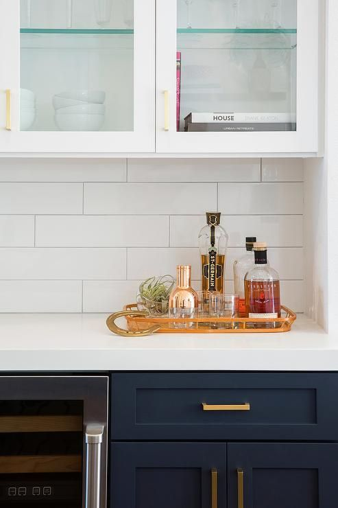 White and blue kitchen features navy blue shaker cabinets adorned aged brass pulls paired with white quartz countertops that resemble marble and a white stacked tile backsplash lined with overhead glass door cabinets.