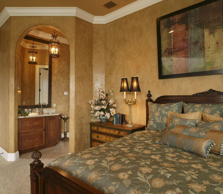 A warm and elegant master bedroom with gold painted walls and green and gold bedding. The room has beige carpet and white crown moulding. We love the colorful wall art above the bed! Click to see how much it costs to remodel your home.