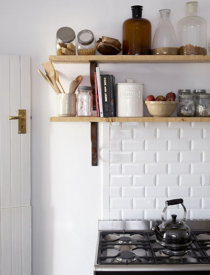 Timber shelves with metal brackets. Collection of glass storage jars and bottles. Interiors by Jean-Pierre de la Chaumette.