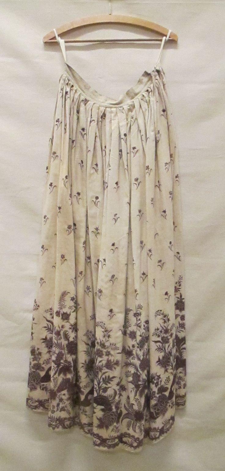 Cotton petticoat/rokken. Rok van witte sits met zwart/paarse opdruk van strooibloemen, onderaan een groot repeterend bloempatroon en een rand van in elkaar slingerende bladertakken c1750-75 Identifier 1050161