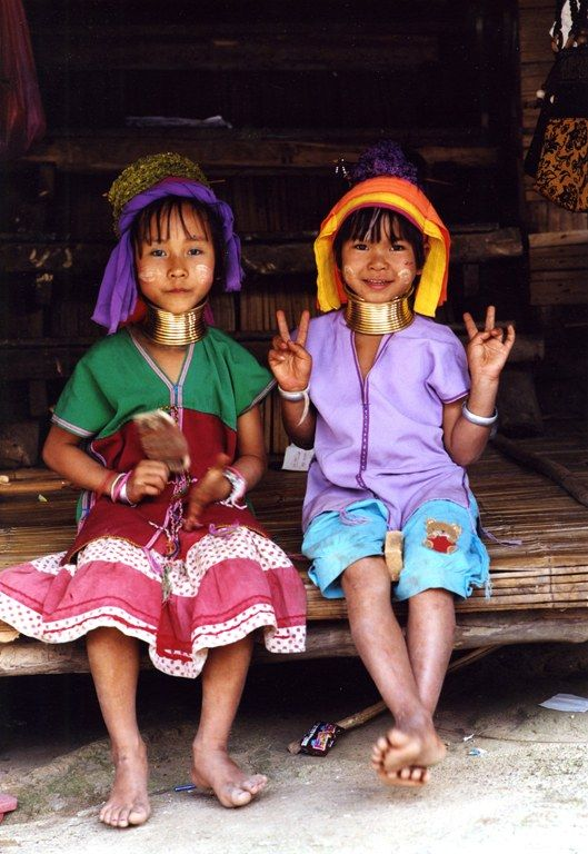 The Padaung are a subgroup of Karen people who live in Thailand and Myanmar. The peace sign is universal.