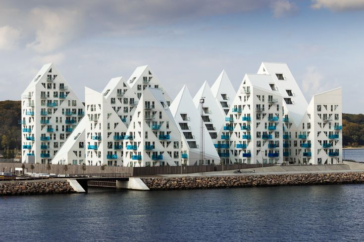 Aarhus, Denmark, a stunning waterfront residential project —the white, unusually shaped building looks just like a giant iceberg. A collaboration between JDS Architects, Cebra, SeARCH and Louis Paillard, the project consists of several pointy-roofed blocks with small, geometric windows cut into their sides. Designed to provide as many occupants as possible with waterfront views, the building wasn't meant to resemble an iceberg initially, but simply came to be so along the way.