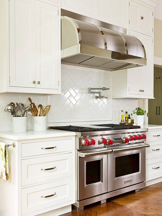 Pretty White Kitchen....love the pretty back-splash and huge, stainless hood and Wolf Stove!