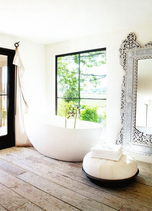 Primitive wood floor w/ Waterworks soaking tub; bone inlay mirror; curtains by Valerie J. Johnson Design; room and ottoman by Erin Martin