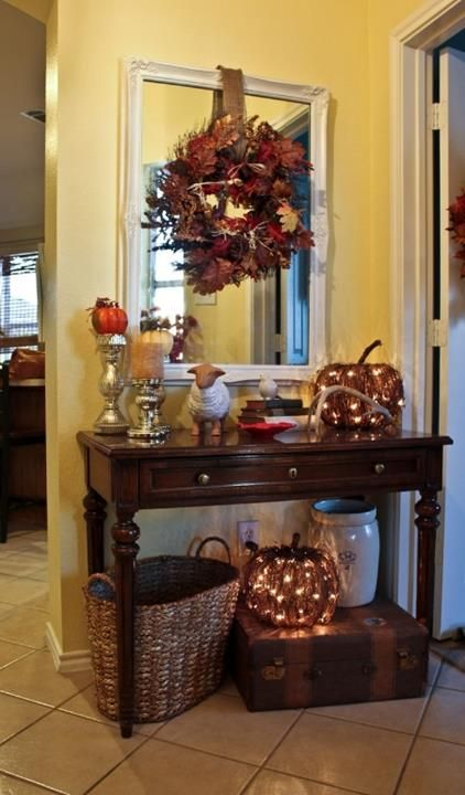 #Entryway #decorations for #fall that glow and sparkle . I like the idea of the lighted pumpkins and a wreath hung over the mirror. Love the vintage touches with the suitcase and jar as well.