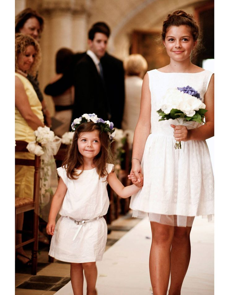Adorable flower girls walking down the aisle. Photograph by Belathée Photography.