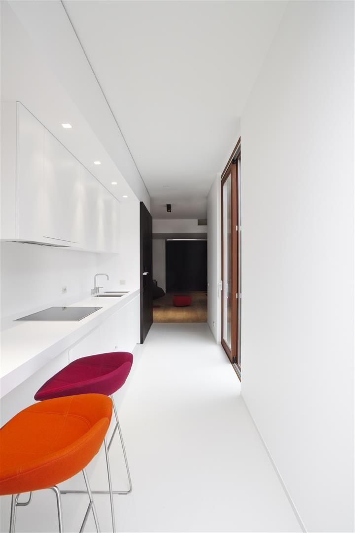 Strakke witte keuken met werkblad in kwarts composiet - ontwerp van Frank Sinnaeve en werkblad van Potier Stone