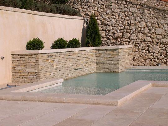 Cette terrasse ainsi que les margelles de la piscine ont été construites en pierre de Bourgogne, et plus précisément en pierre Bois Doré, extraite dans le Bassin Châtillonnais. D'un beige éclatant, légèrement orangé, elle met en valeur la couleur de l'eau. Le muret est en pierre de l'Yonne. (source Cotemaison.fr)