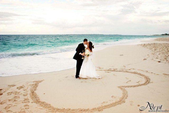 photo de mariage: bisou au milieu d'un coeur dessiné sur le sable