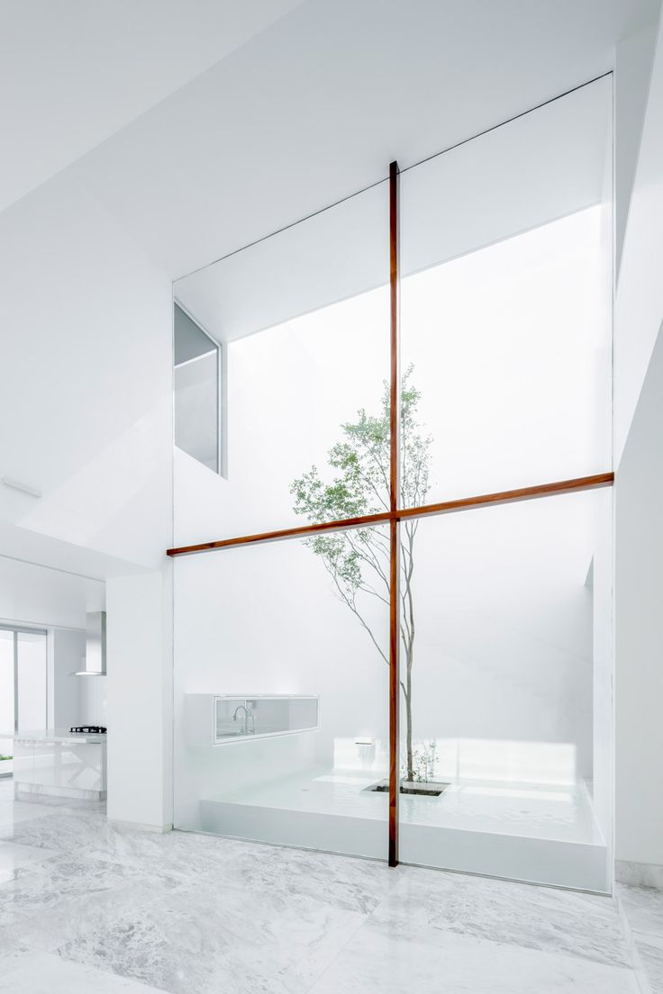 A spindly crucifix-like frame supports a huge window overlooking a patio inside this Mexican residence