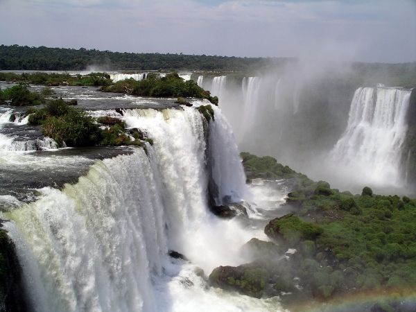 The mighty Iguazu Falls in Brazil are a UNESCO Site This national park, shared by Brazil and Argentina, is named after the Iguazu River and the Iguazu Falls in Parana State and is the most famous of Brazil's UNESCO World Heritage Sites. Many endangered species, such as the giant anteater and the giant otter. The waterfall is partly responsible for the lushness of the Iguazu National Park, which was named a World Heritage Site in 1986.