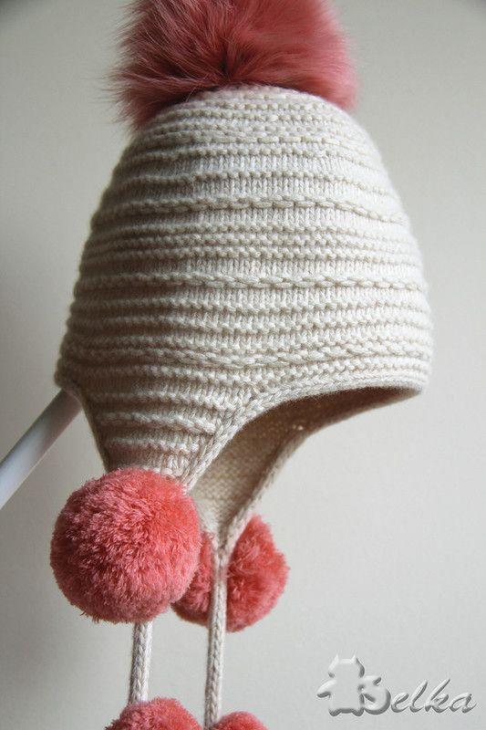 Саму шапку связала простым поперечным узором, чтобы сместить акцент на украшение помпонами. В поперечном узоре чередуются рубчики платочной вязки и горизонтальные цепочки.  Шапка связана, начиная с завязок, затем ушки с полым шнурком по краям. Потом на продолжении этого полого шнура набирала петли на затылок и переднюю часть. Т.е. получается, что вся шапка цельновязанная с шнуром.