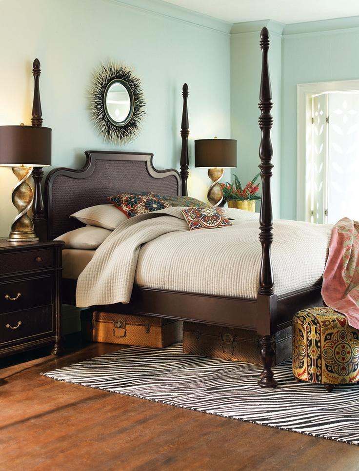 Colonial style home with four poster bed, trunks, natural color scheme, and a clean, uncluttered aesthetic.