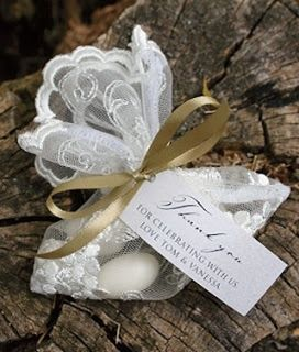 """Colocar una gardenia y un """"costalito"""" de organza blanco o marfil o una cajita transparente, con 5 almendras confitadas, que se amarraran con un listón delgadito en organza y satín. Se acompañara de una tarjetita que describa la tradición. Y el origen de los confites de almendras."""