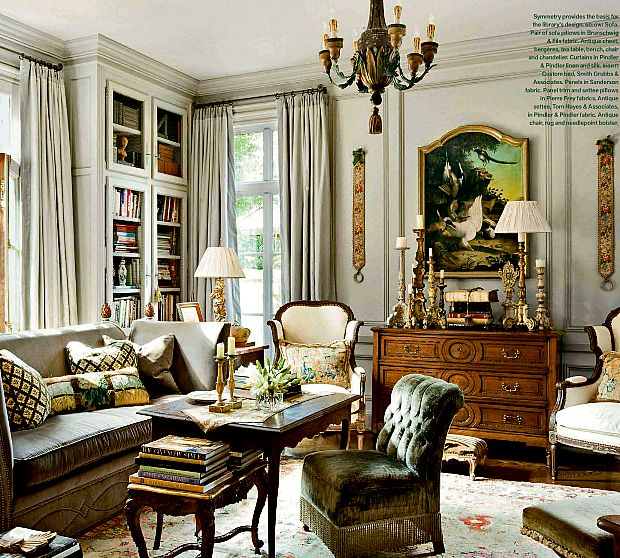 A high French antique end table is used here. When you use a high table like this, you can add a short chair in front – as shown. This owner also layered another shorter table under the higher one. Love this look.