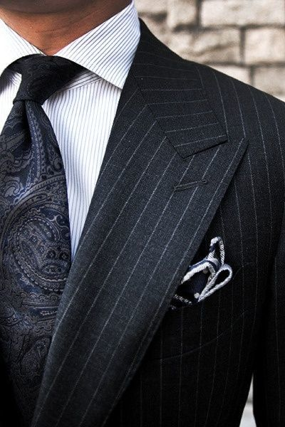 Nail that dapper look with a black vertical striped suit and a white striped oxford shirt.   Shop this look on Lookastic: https://lookastic.com/men/looks/black-suit-white-dress-shirt-black-tie/19365   — White Vertical Striped Dress Shirt  — Black Paisley Tie  — Black Vertical Striped Suit  — Black and White Polka Dot Pocket Square