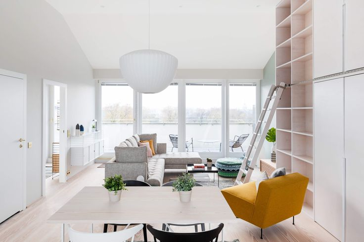 Modern private residence in Krakow by Studio Mills. Lounge and dining area complete with plywood library wall and ladder #plywood #livingroom #scandinavian