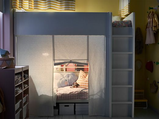 A shared kids' room at night with a loft bed and a bed underneath that has a privacy curtain