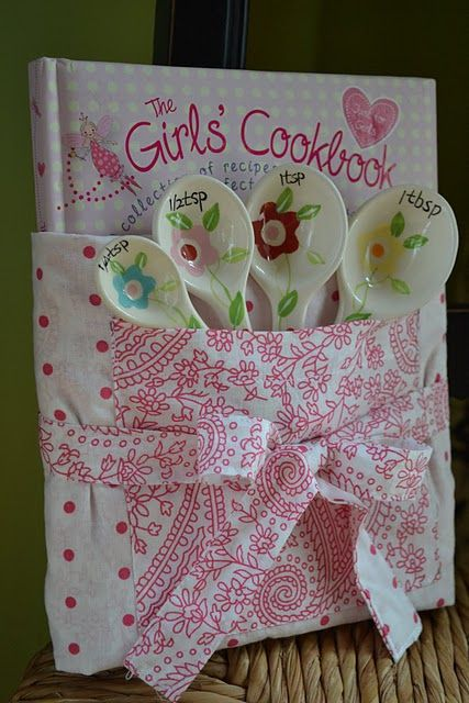 """""""The Girl's Cookbook"""" wrapped in a child's apron with cute measuring spoons in the pocket"""