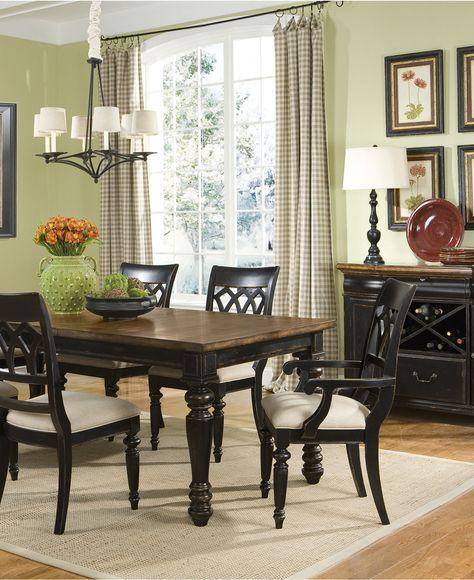 Деревянная вычурная мебель черного цвета гармонирует со спокойным цветом стен столовой.