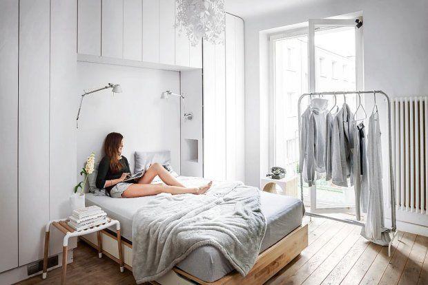 W sypialni całą  ścianę wokół łóżka (IKEA) zajmują szafy. Po bokach lampy Artemide.