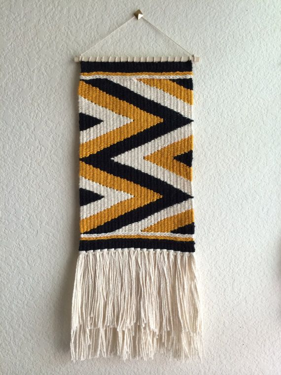 One handmade woven wall hanging. Measures approximately 8 in (w) x 20 in (L)  Colors: black, mustard, natural