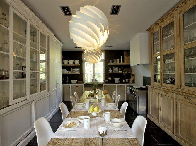 De chaque côté de la table, une vitrine de pharmacie en pin et un vaisselier en bois, réalisé sur mesure et peint en blanc, se font face. Dans le coin cuisine, des étagères en chêne massif se détachent sur fond noir et encadrent la fenêtre.