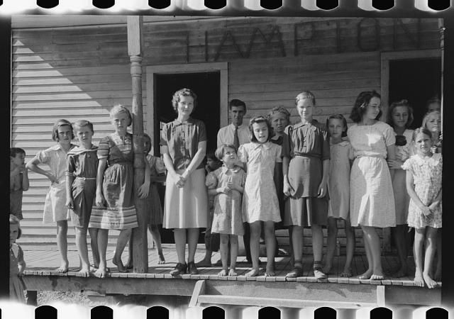mountain children with teacher in front of schoolhouse