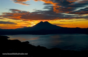 This is not a sunset but a sunrise at lake of Ilopango in San Salvador with the twin peaked Chinchotepeq volcano in the background.  Beautiful combination of colours!