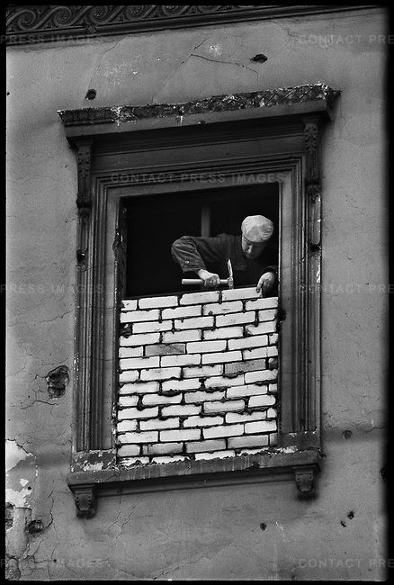 Windows in East Berlin near the construction of the Berlin Wall are bricked up. Viewed from West Berlin, German, November 1961.