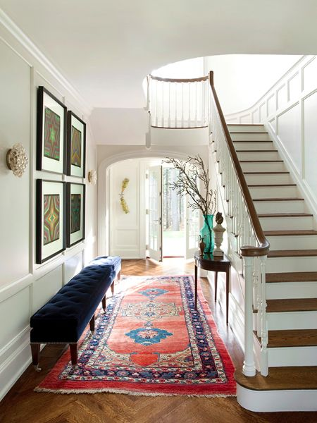 """Designer Frank Roop used an oversize tufted bench to add an """"unexpected or dramatic"""" element to the entryway of this Boston-area colonial home."""